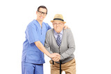 Male healthcare professional assisting an old man with cane