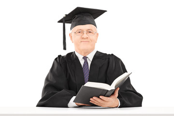 Mature man in graduation gown holding a book