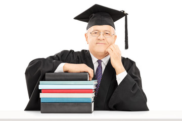 Middle aged college professor posing with a stack of books