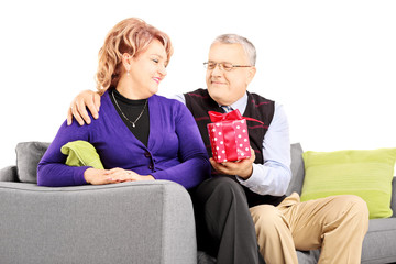 Middle aged man giving a present to his wife