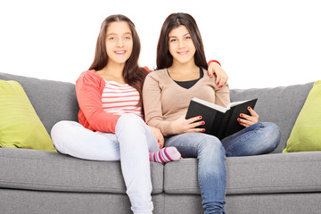 Two girls seated on sofa hugging and looking at camera
