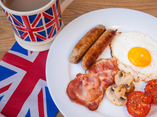 Close-up of Bacon and eggs with cup of tea and british flag