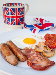 english breakfast  with cup of tea and british flag behind