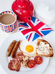 Bacon,  eggs and sausages with cup of tea, teapot, toast and bri