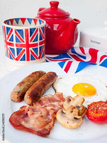 Bacon and eggs with cup of tea and british flag behind