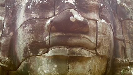 Stone face on the tower of the ancient temple. Bayon, Angkor, Ca