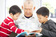 grandfather and grandchildren reading a book