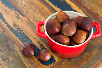 Chestnut in red bowl on wooden table. Selective focus