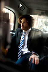 Handsome business executive inside taxi cab