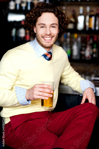 Young guy having chilled beer at bar