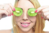 Young woman with fresh kiwi fruit
