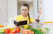 Woman cooking  veggie food with book