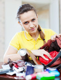 inconsiderate woman  searching something in handbag
