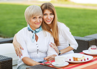 adult mother and daughter drinking tea or coffee and talking