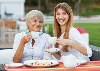 Adult mother and daughter drinking tea or coffee.