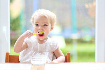 Smiling little blonde toddler girl eating delicious yogurt