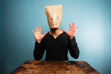 Stupid man with bag over his head and hands up