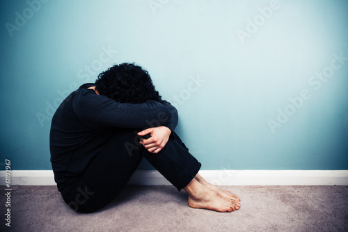 Sad man sitting on floor