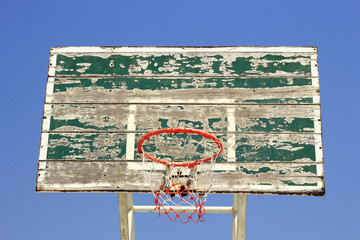 Old crack basketball board with  hoop on blue sky background