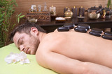 Traditional thai massage - man getting hotstone treatment