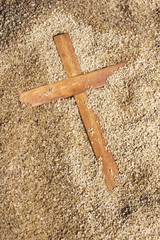Forgotten Wooden Cross on Sand Texture Background