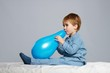 Little boy in blue pyjamas having fun with balloon in bed