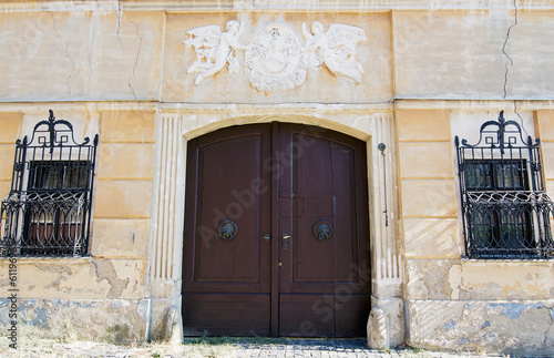Old house with coat of arms above the wooden gate