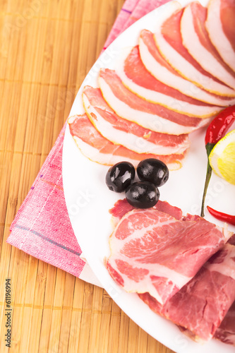 Sliced meat on the white plate with chili pepper and lemon