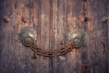 Closed lock with a chain on a wooden door