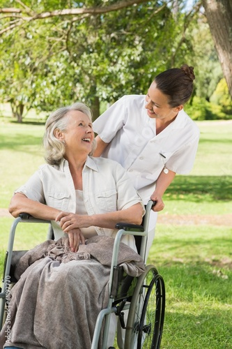Woman with her mother sitting in wheel chair at park