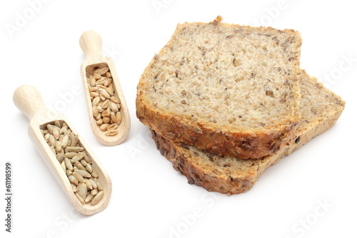 Natural rye and wheat grain on wooden spoons and bread