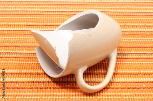 Broken mug, shattered cup on orange cloth
