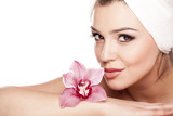 Fototapety woman with a towel on her head enjoying the scent of orchids