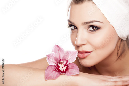 woman with a towel on her head enjoying the scent of orchids