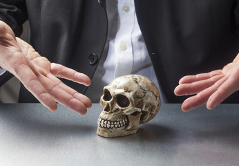 male hands presenting a skull for scientific purpose
