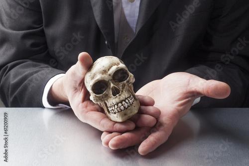 doctor's hands displaying a skull
