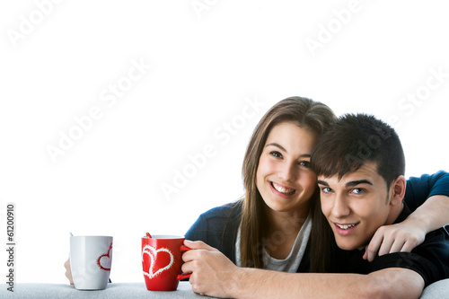 Teen couple with coffee mugs.