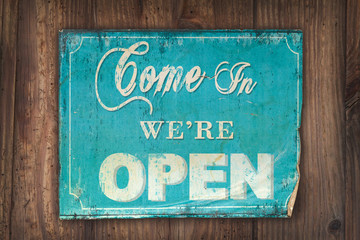 Come in we're open sign on an old wooden background