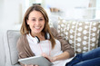 Smiling young woman websurfing with tablet at home
