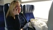 attractive blonde women talking smartphone in a train