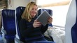 attractive blonde women using digital tablet in a train