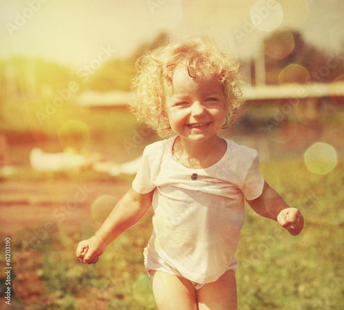 Happy little girl in summer sunlight. Vintage paper textured