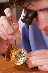 Watchmaker viewing closely at an antique pocket watch