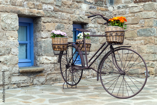 Rusty bicycle in front of a traditional house in Epirus, Greece © dinosmichail