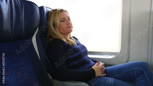 attractive blonde women trying to sleep in a train