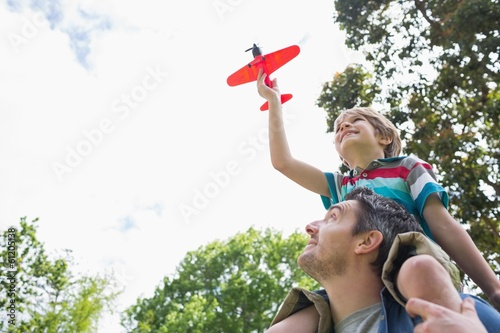 Boy with toy aeroplane sitting on father's shoulders