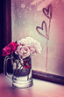 White roses in a glass vase with heart
