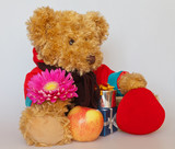 Cute Teddy Bear in a jacket with gifts and flower