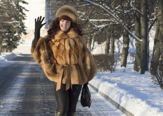 The attractive woman in a fox fur coat is photographed in winter