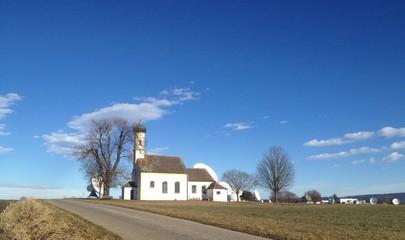 Kleine Kirche vor Satellitenschüsseln
